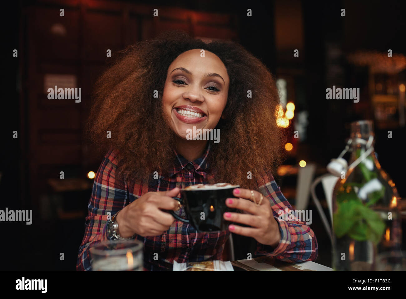 Portrait of young woman drinking coffee. African woman sitting at cafe holding a cup of coffee, looking at camera - Stock Image