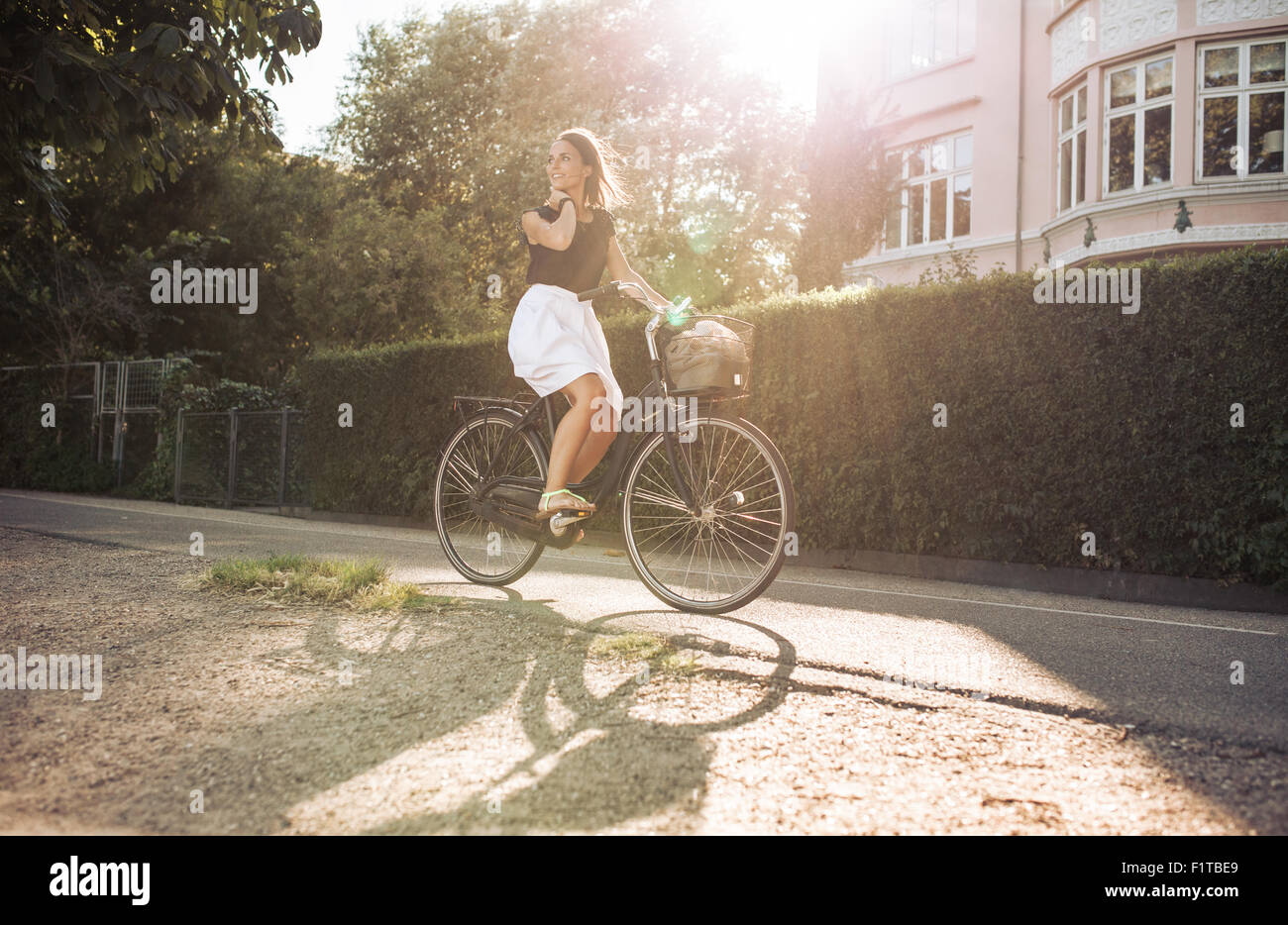 Pretty young woman enjoying bicycle ride through the street. Female looking away smiling while cycling. Stock Photo