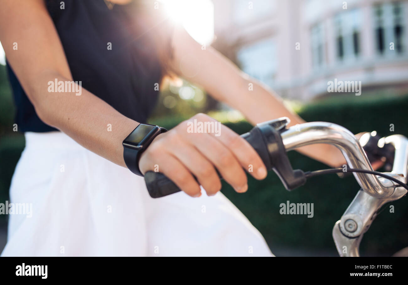 Woman riding a bike with a smartwatch. Female wearing smart watch while cycling. Smart watch concept. - Stock Image