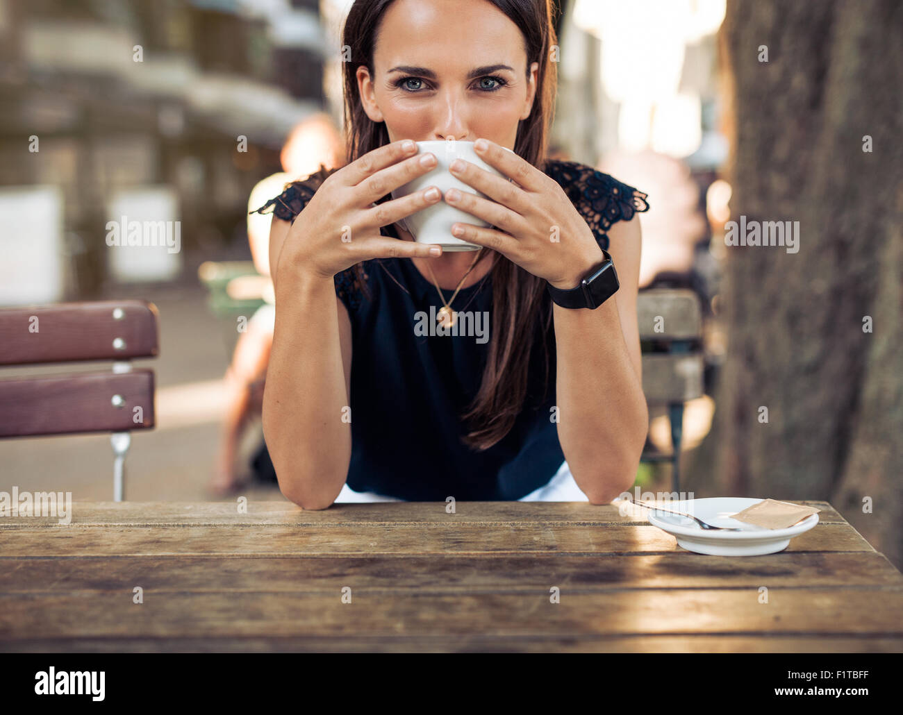 Young woman drinking coffee at a cafe and looking at the camera. Caucasian female sitting at table having a cup - Stock Image