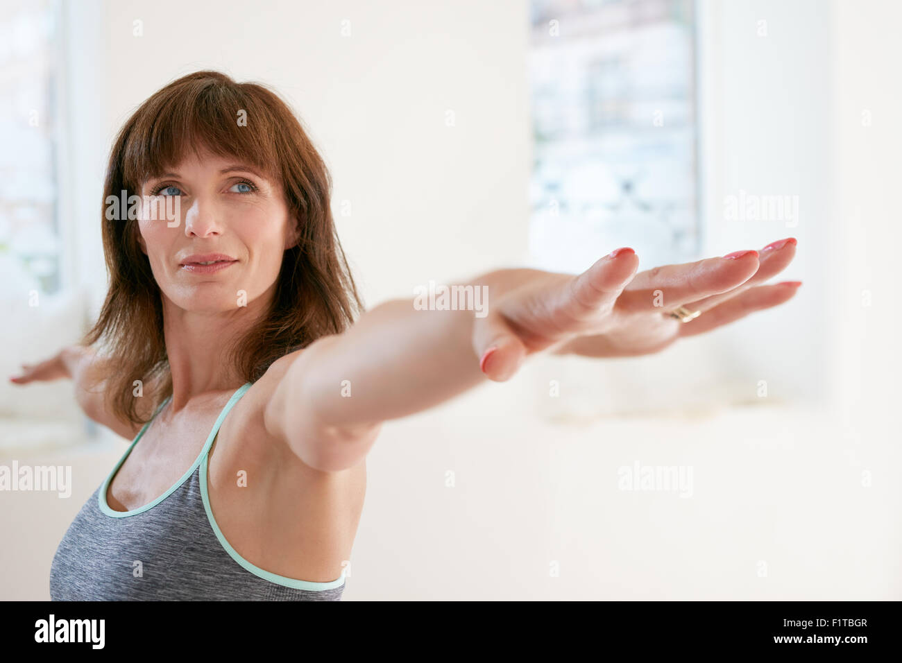 Portrait of fitness woman stretching her hands and looking away. Attractive mature woman exercising yoga in Virabhadrasana - Stock Image