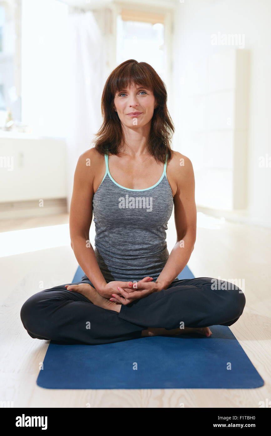 Vertical shot of fit woman sitting on exercise mat with her legs crossed at knee and hands joined meditating. Female - Stock Image