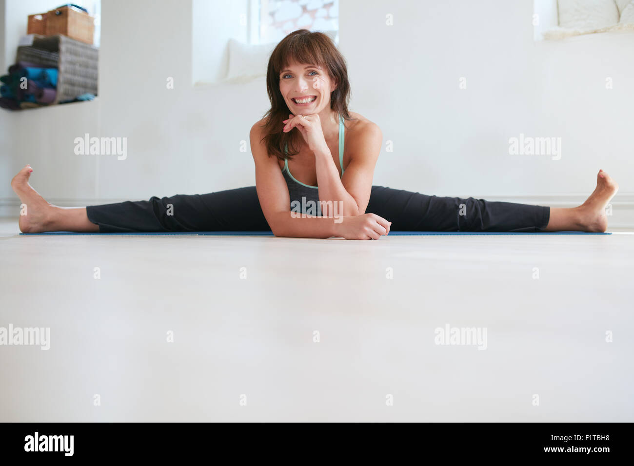 Happy woman doing wide angle seated forward bend yoga at gym. Fitness female practicing Upavistha Konasana yoga. - Stock Image