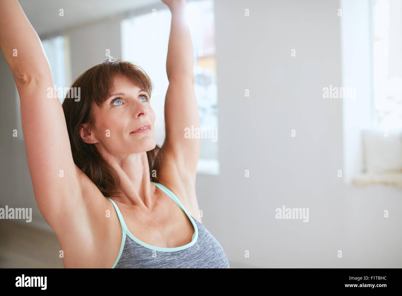 Close up shot of mature woman practicing yoga with her arms raised and looking upwards at gym. Fitness female in - Stock Image