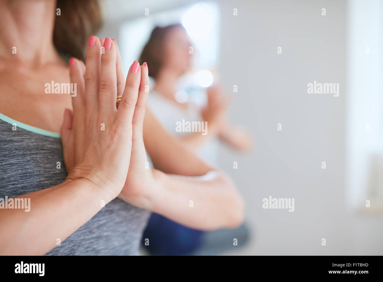 Close up shot of women at yoga class meditating with hands clasped. Female hands in namaste gesture during yoga Stock Photo
