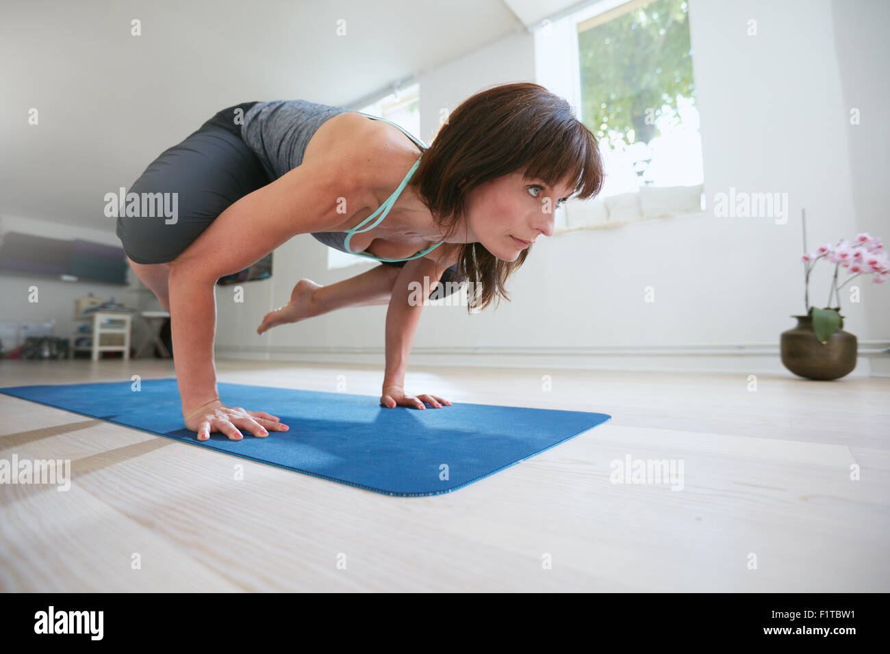 Mature fitness woman standing on hands with feet lifted up doing crane yoga pose - Bakasana. Woman doing hands stand - Stock Image