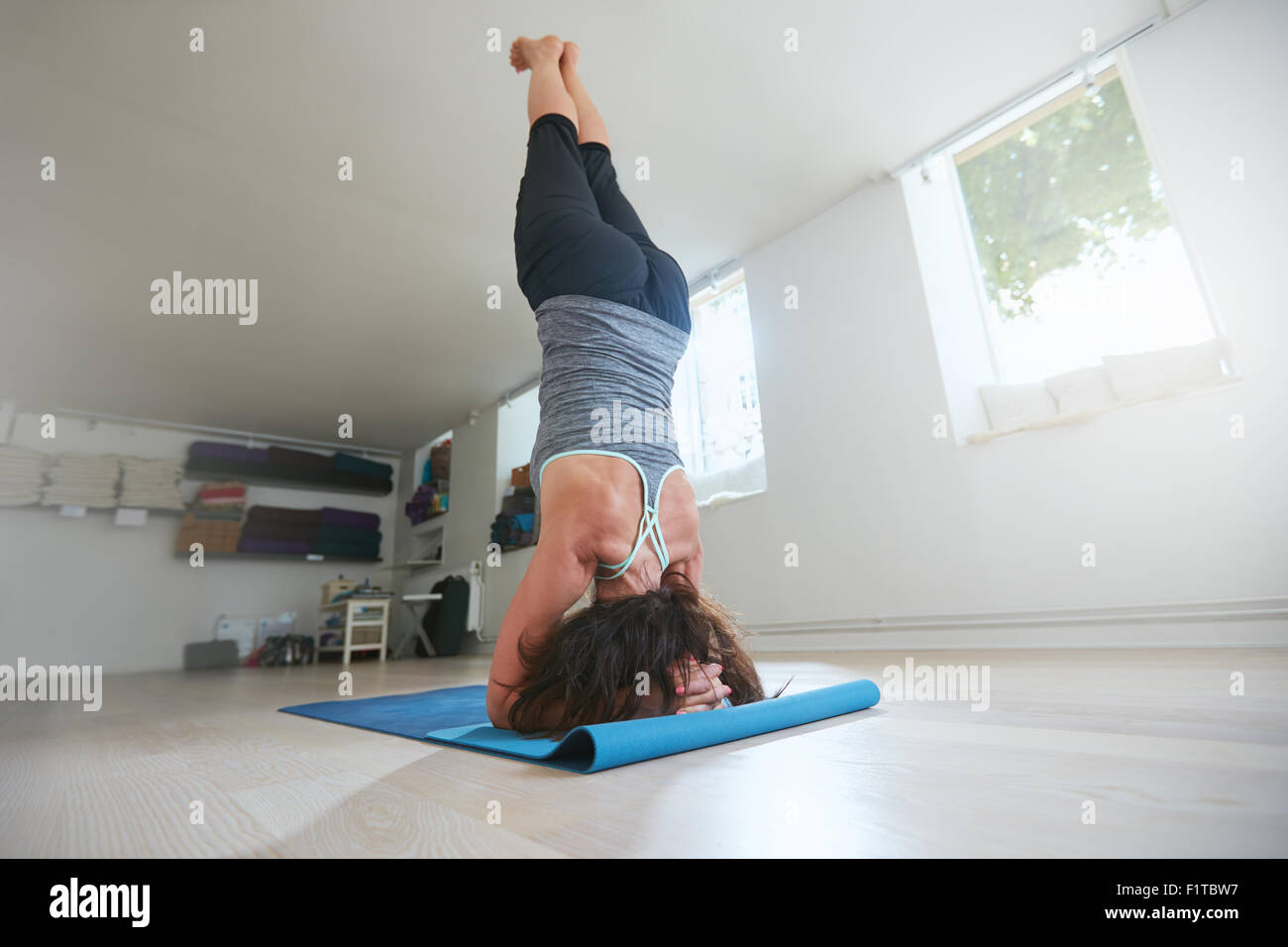 Sporty woman practice yoga, doing supported headstand yoga asana. Rear view of fitness female practicing Salamba - Stock Image