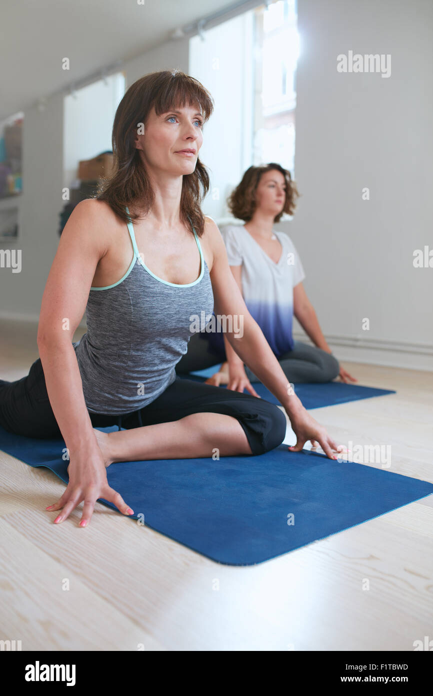 Female fitness instructor at yoga class in pigeon pose on her yoga mat in gym. Women at yoga class practicing Kapotasaana. - Stock Image