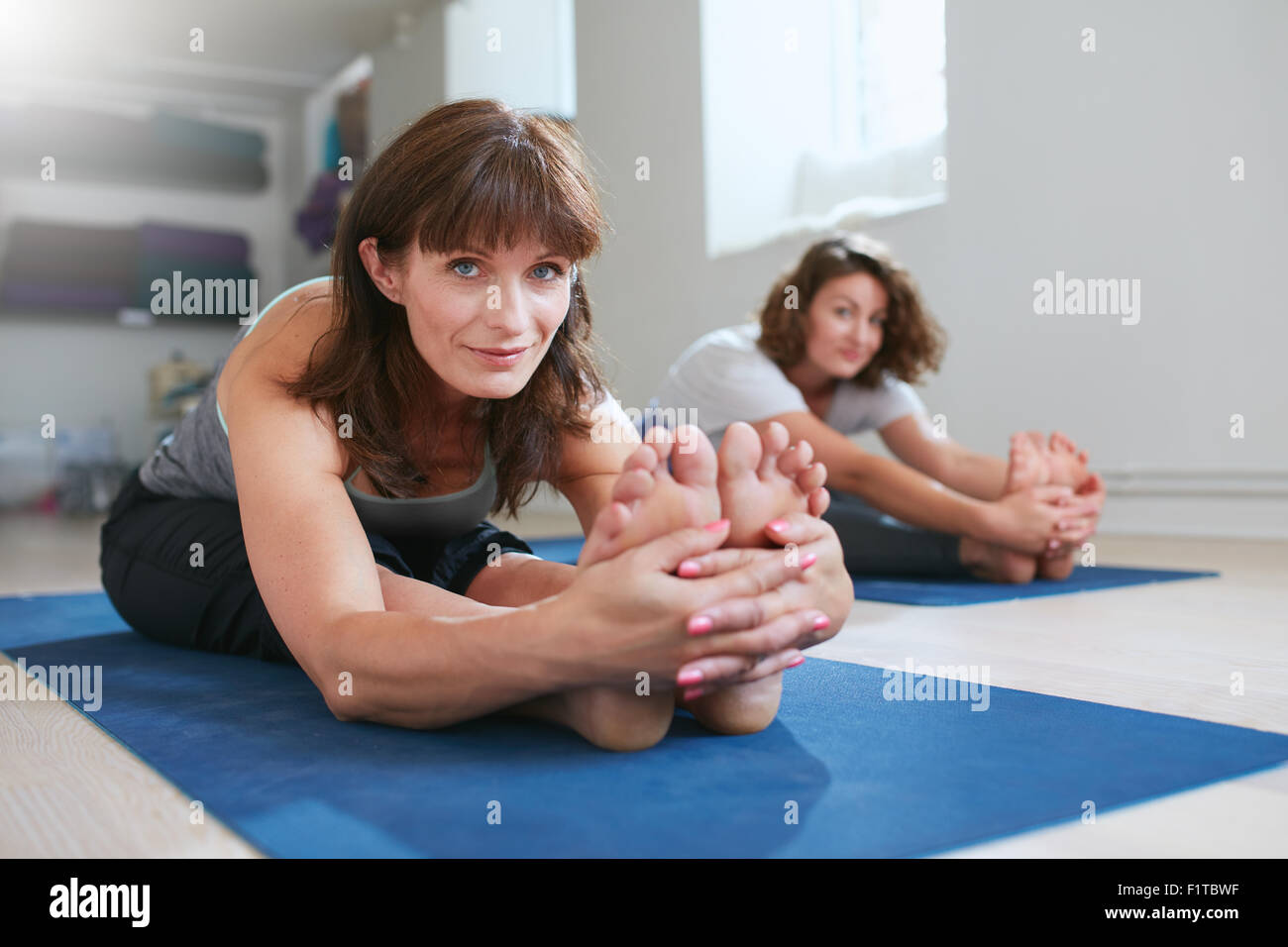 Women doing yoga together at gym, practicing paschimottanasana pose. Fitness female seated forward bend pose during Stock Photo