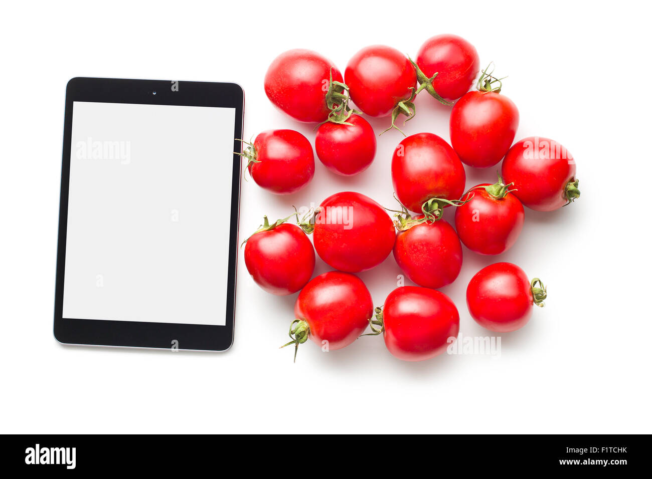 computer tablet and tomatoes on white background - Stock Image