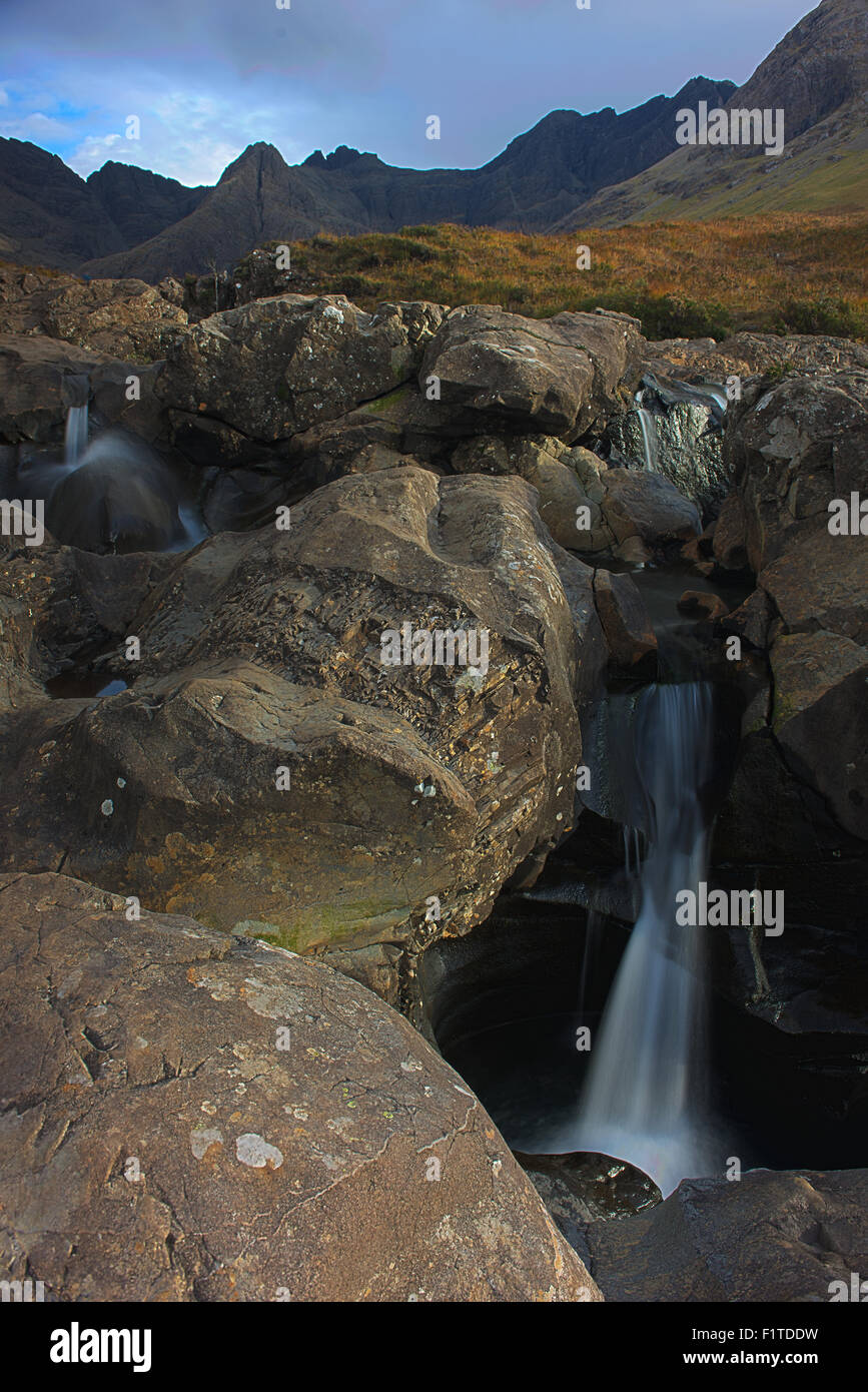 Water cascades from pool to pool at the Fairy Pools on the Isle of Skye.  The Black Cuillins are in the distance. - Stock Image