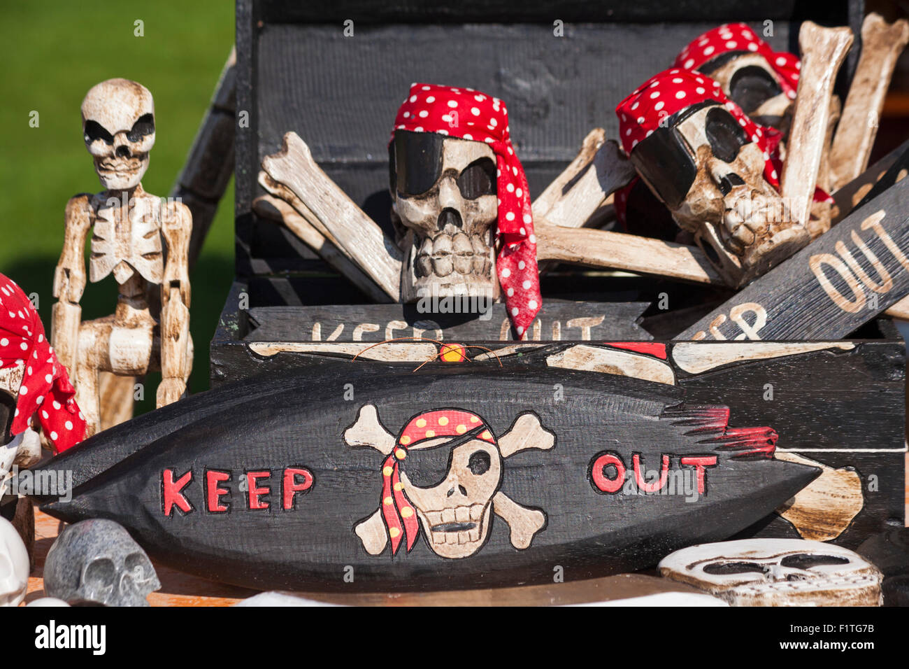 Keep out sign and skull & crossbones for sale on stall at Poole Thai Festival, Dorset, UK in September - Stock Image