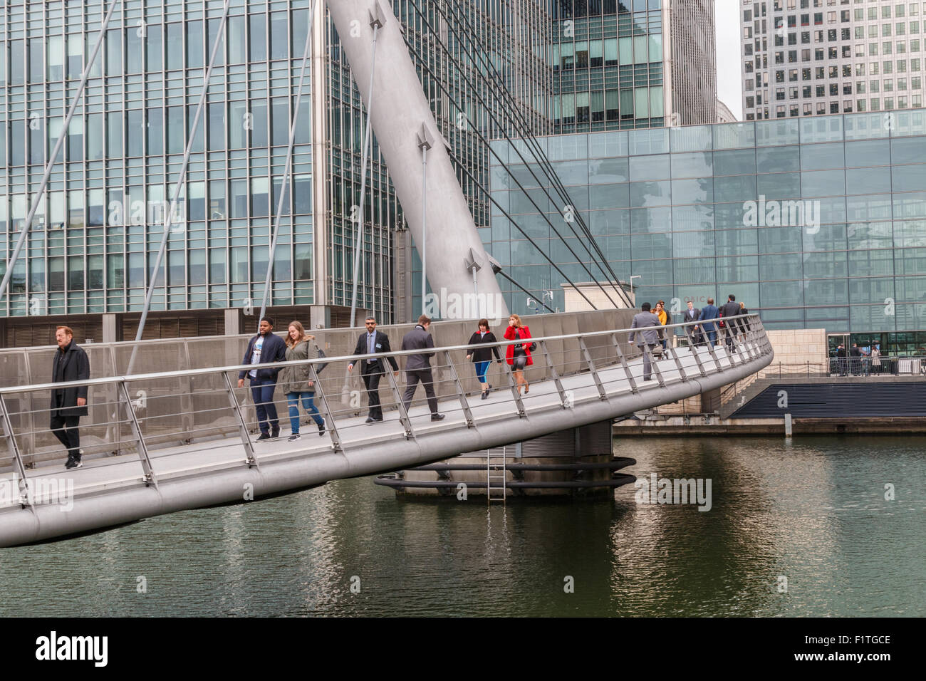 Office workers crossing Wilkinson bridge in London's Canary Wharf - in the docklands - Stock Image