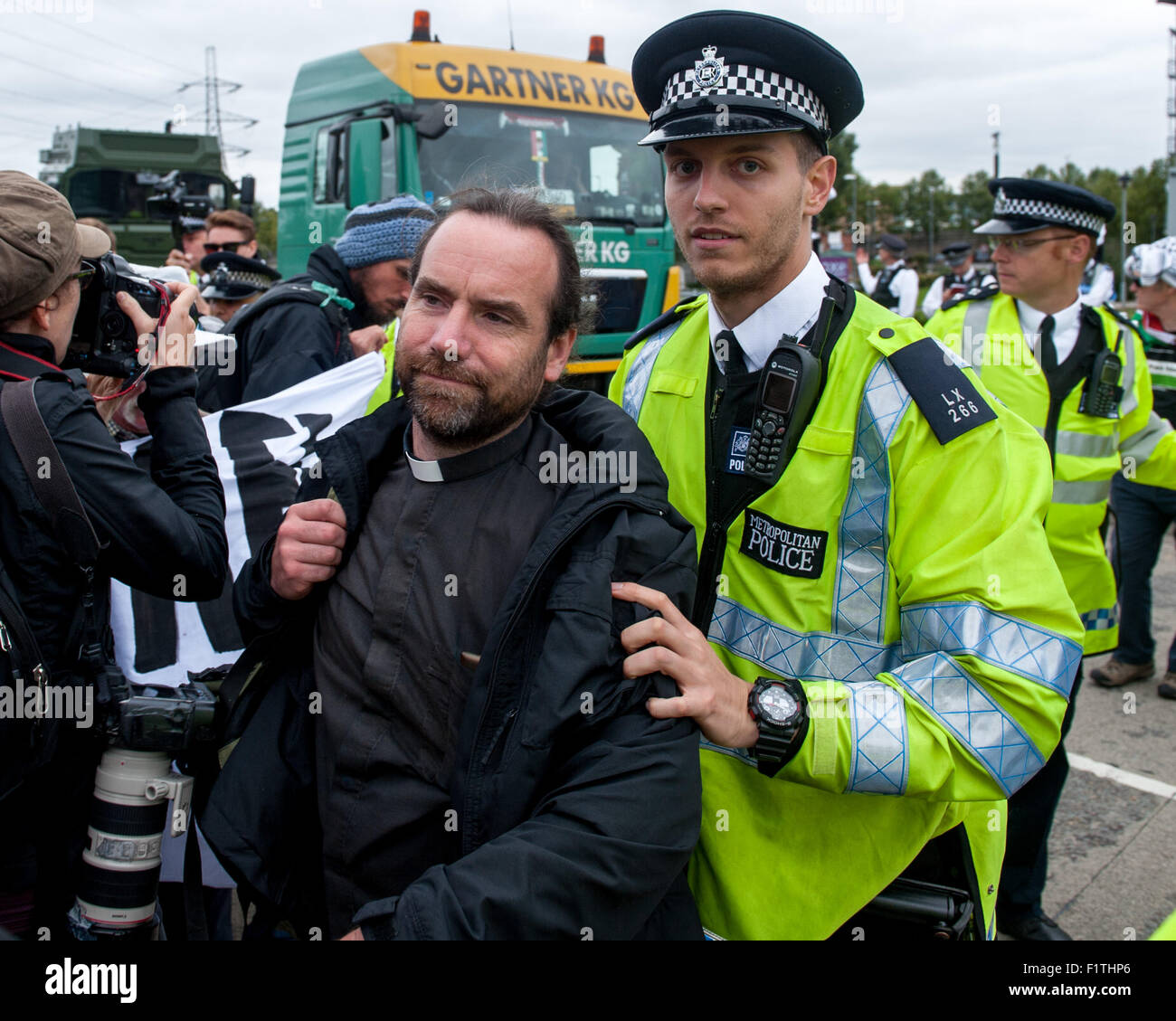 London, UK. 7th September, 2015. Police remove a vicar from the blockade during a protest against the DSEI, one Stock Photo