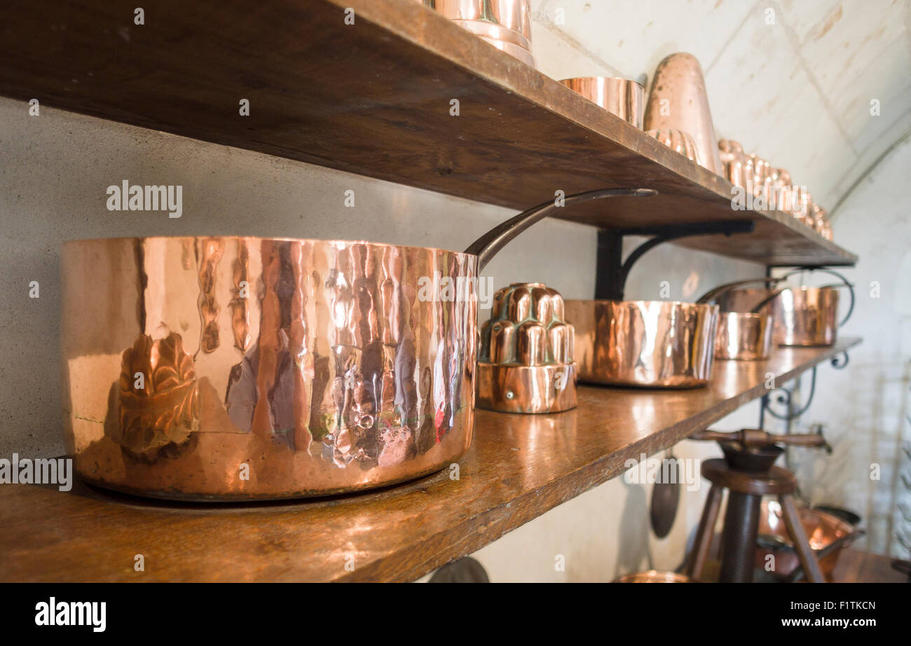 A shelf of shiny copper pots. A kitchen shelf dedicated to the display of fine old copper clad pots and other kitchen - Stock Image