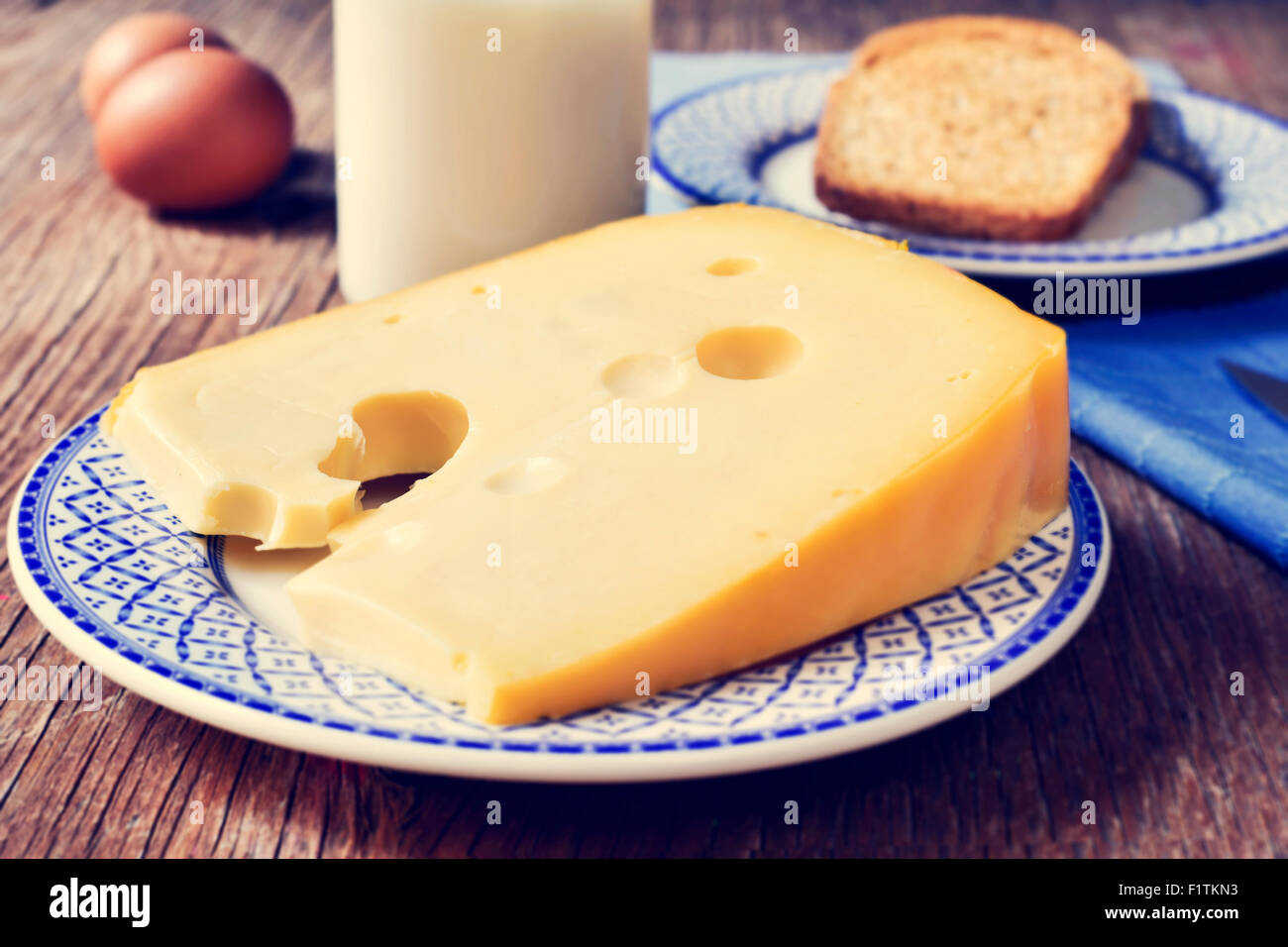 closeup of a piece of Swiss cheese in a plate, a bottle with milk, some brown eggs and a plate with some toasts - Stock Image