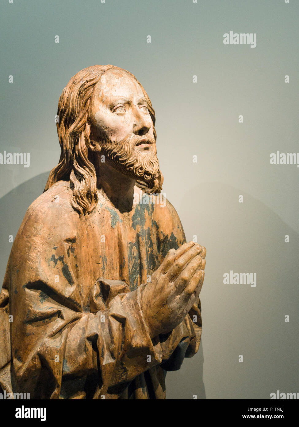 Medieval Wooden sculpture of Christ Praying. A worn statue of a praying Christ figure, its paint flaking off to Stock Photo