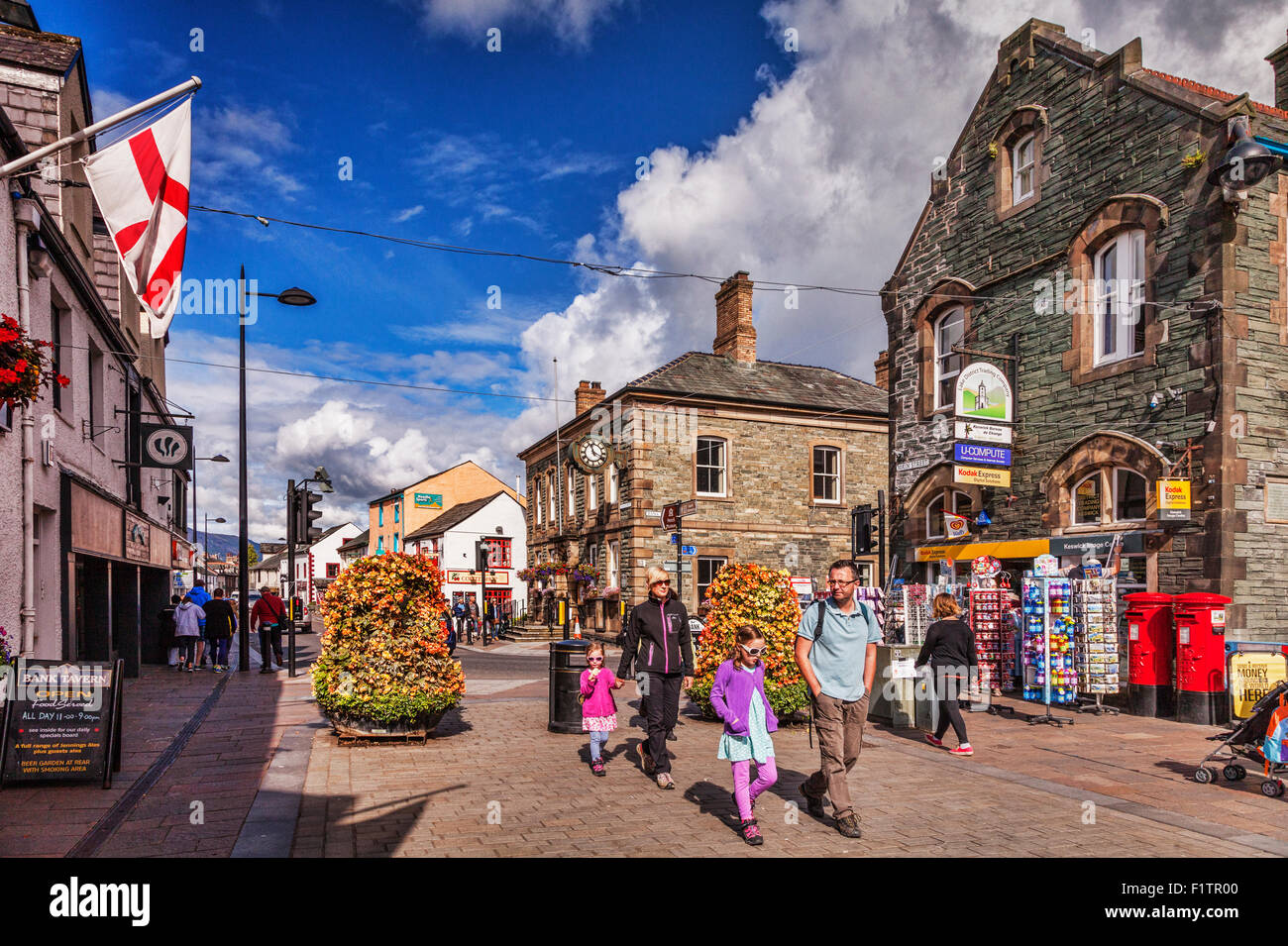 Tourists strolling in Keswick High Street on a sunny autumn day, Cumbria, England. - Stock Image