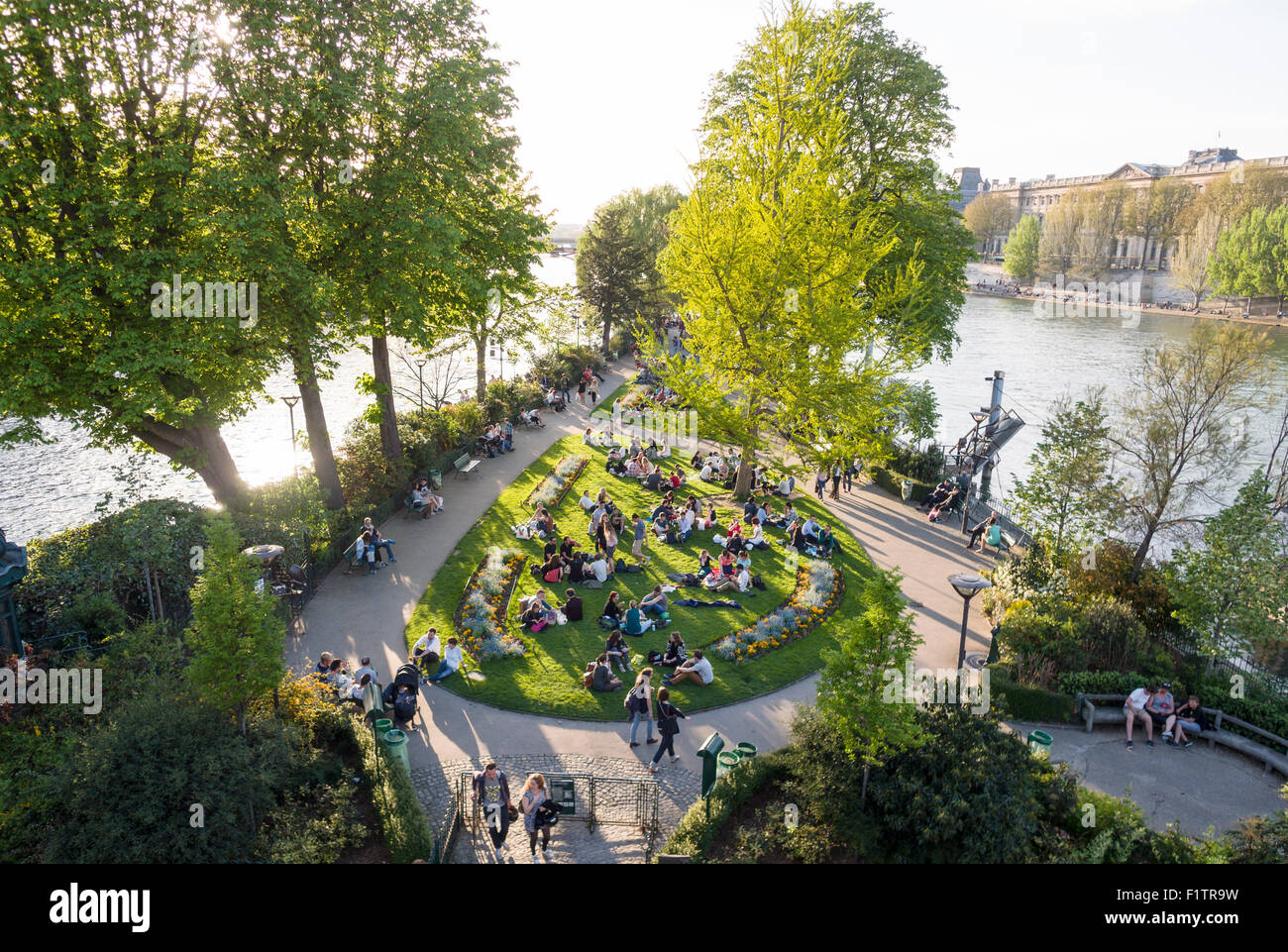 Park at the tip in the Seine . Tourists and locals enjoy the evening sunshine at the tip of the Île de la Cité Stock Photo