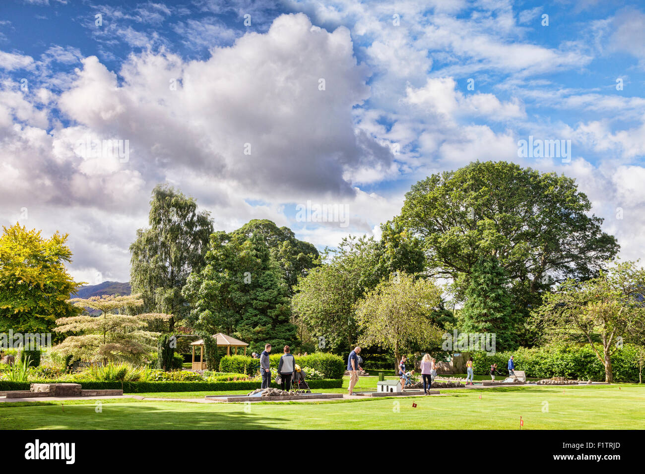 Tourists playing Crazy Golf in Hope Park, Keswick, Cumbria, England. - Stock Image