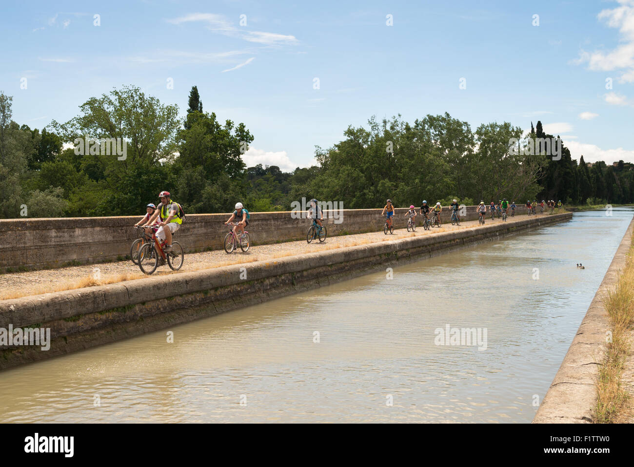 A group of schoolchildren cycling across the Orb aqueduct of the Canal du Midi, Béziers, Languedoc-Roussillon, - Stock Image