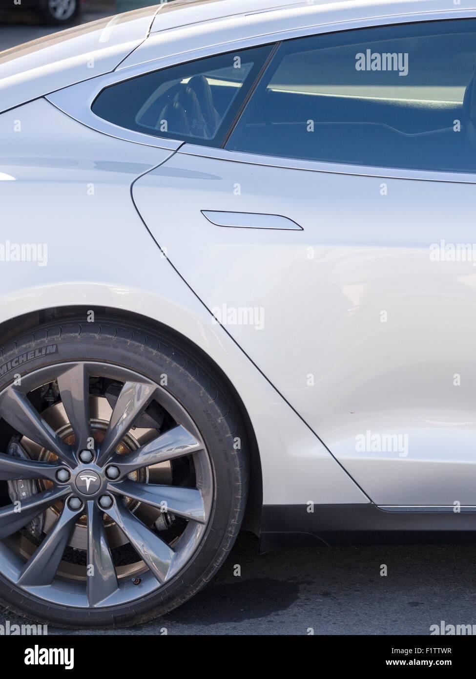 Tesla  model S rear door . The rear door, window and wheel of a parked Tesla model S in a Wiamea parking lot. - Stock Image