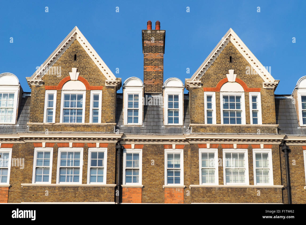 Facade of buildings in London with traditional roofs and a chimney - Stock Image