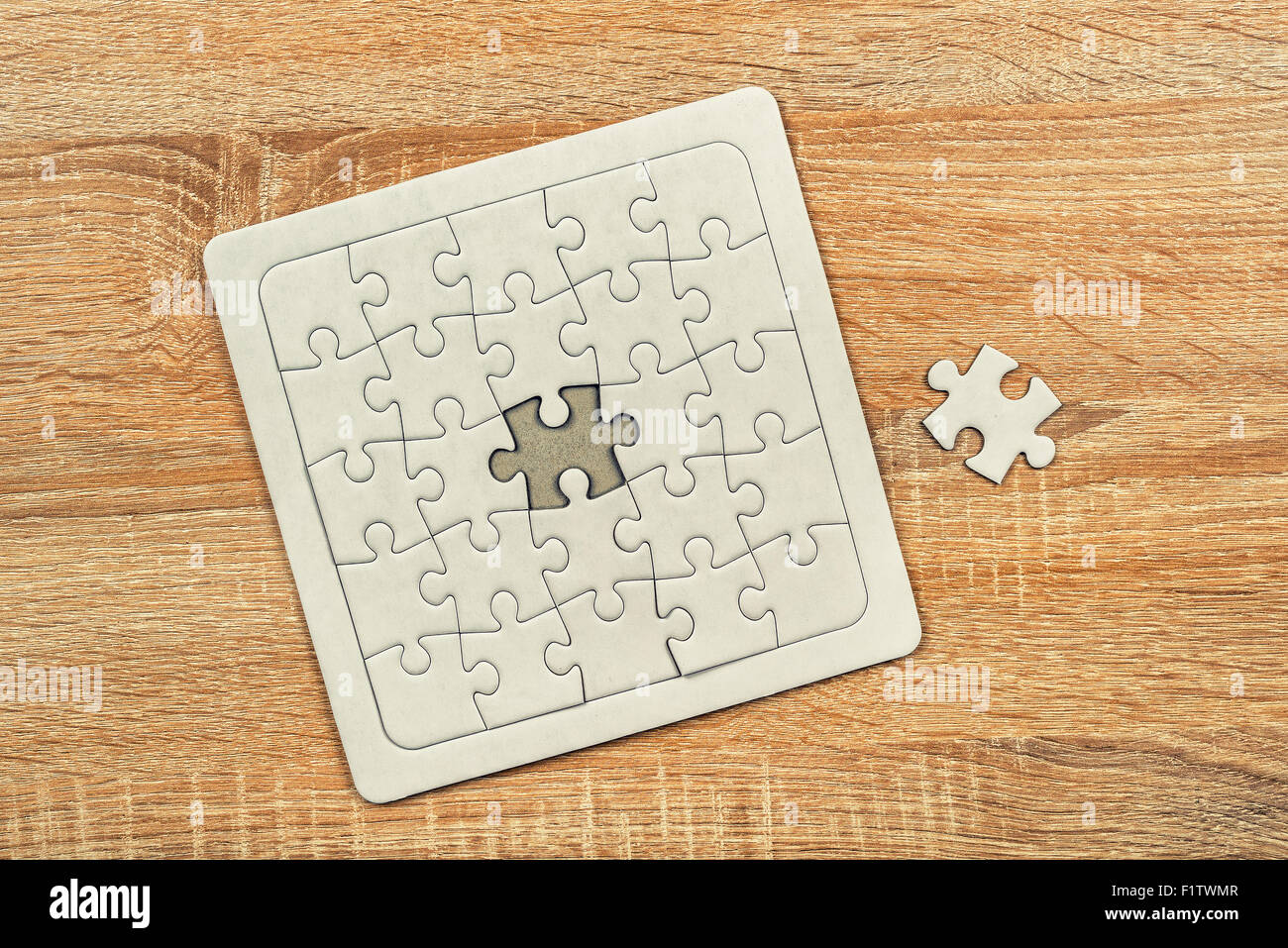 Piece missing from jigsaw puzzle as copy space placed on top of old wooden oak table, top view Stock Photo