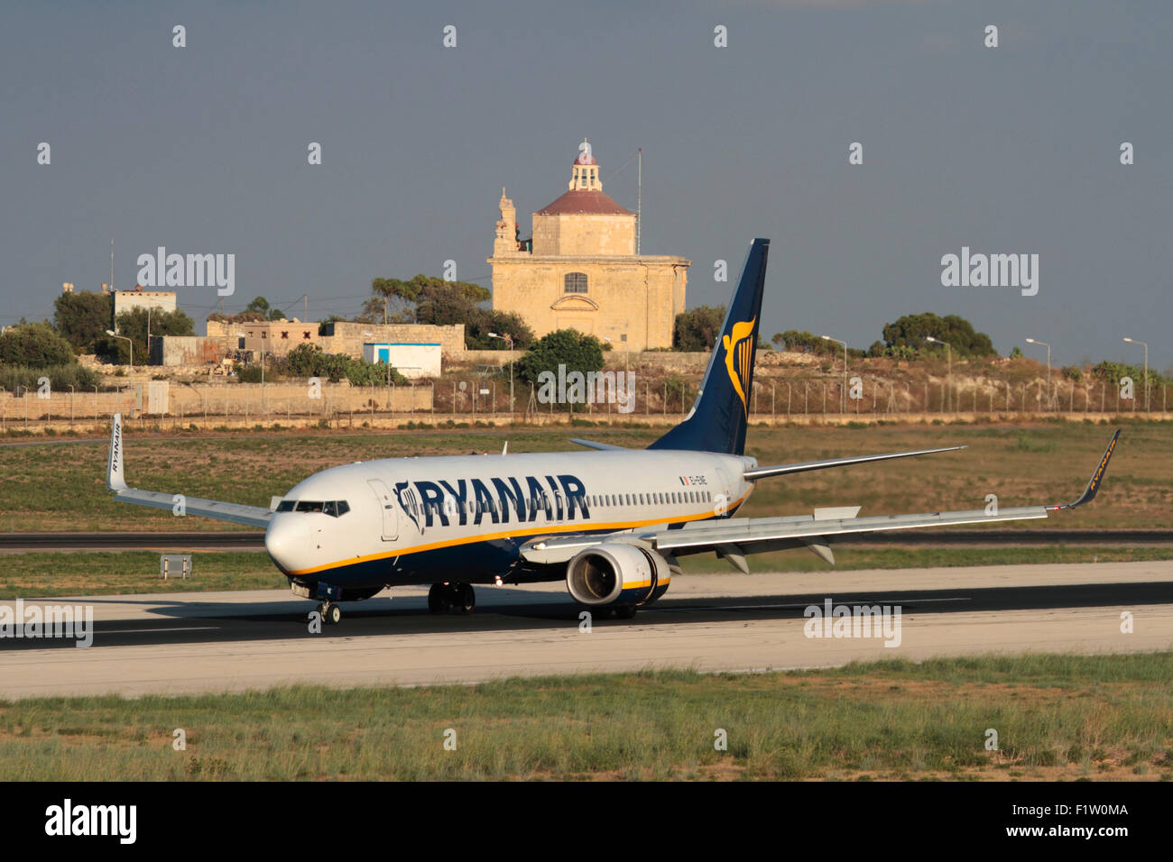 Low cost air travel in the EU. Ryanair Boeing 737-800 jet plane on arrival in Malta, with Ta' Loretu chapel, - Stock Image