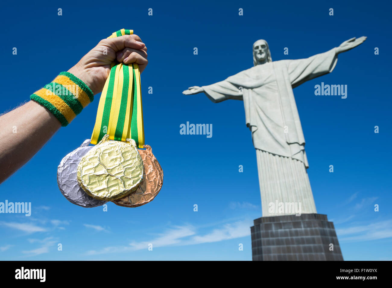 RIO DE JANEIRO, BRAZIL - MARCH 05, 2015: Hand holds gold medals hanging from Brazil color ribbons in clear blue - Stock Image
