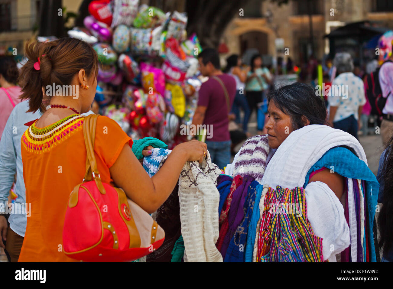 Buying a shawl in the ZOCALO or central plaza - OAXACA, MEXICO - Stock Image