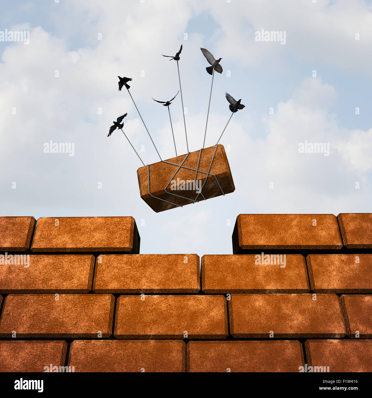 Build a wall business concept as a group of birds placing a brick to complete a wall as a puzzle metaphor and working - Stock Image
