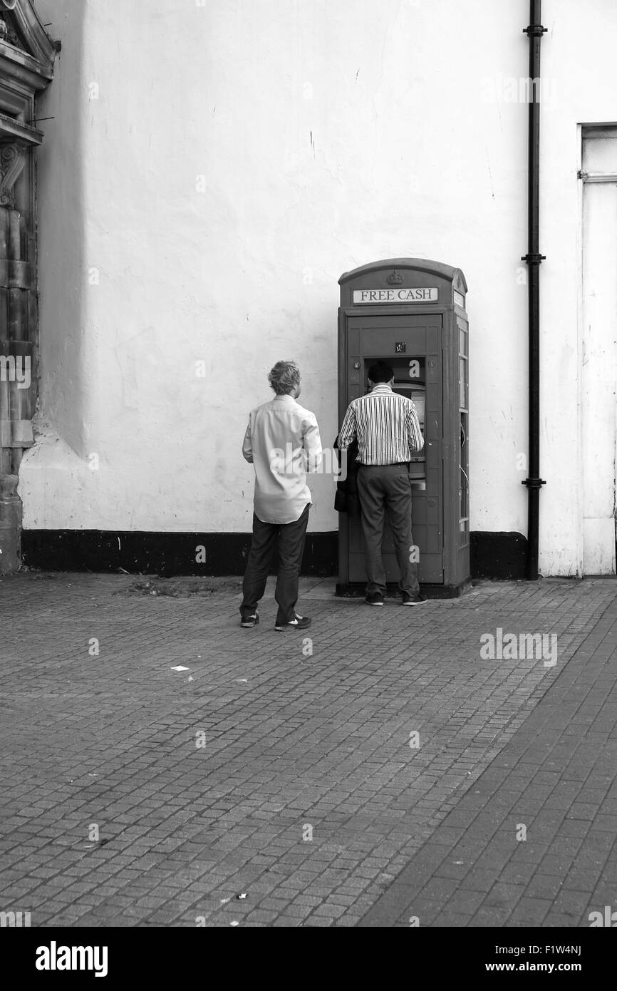 Two men queuing at a ATM cash point machine in an old old traditional telephone box. September 2015 - Stock Image