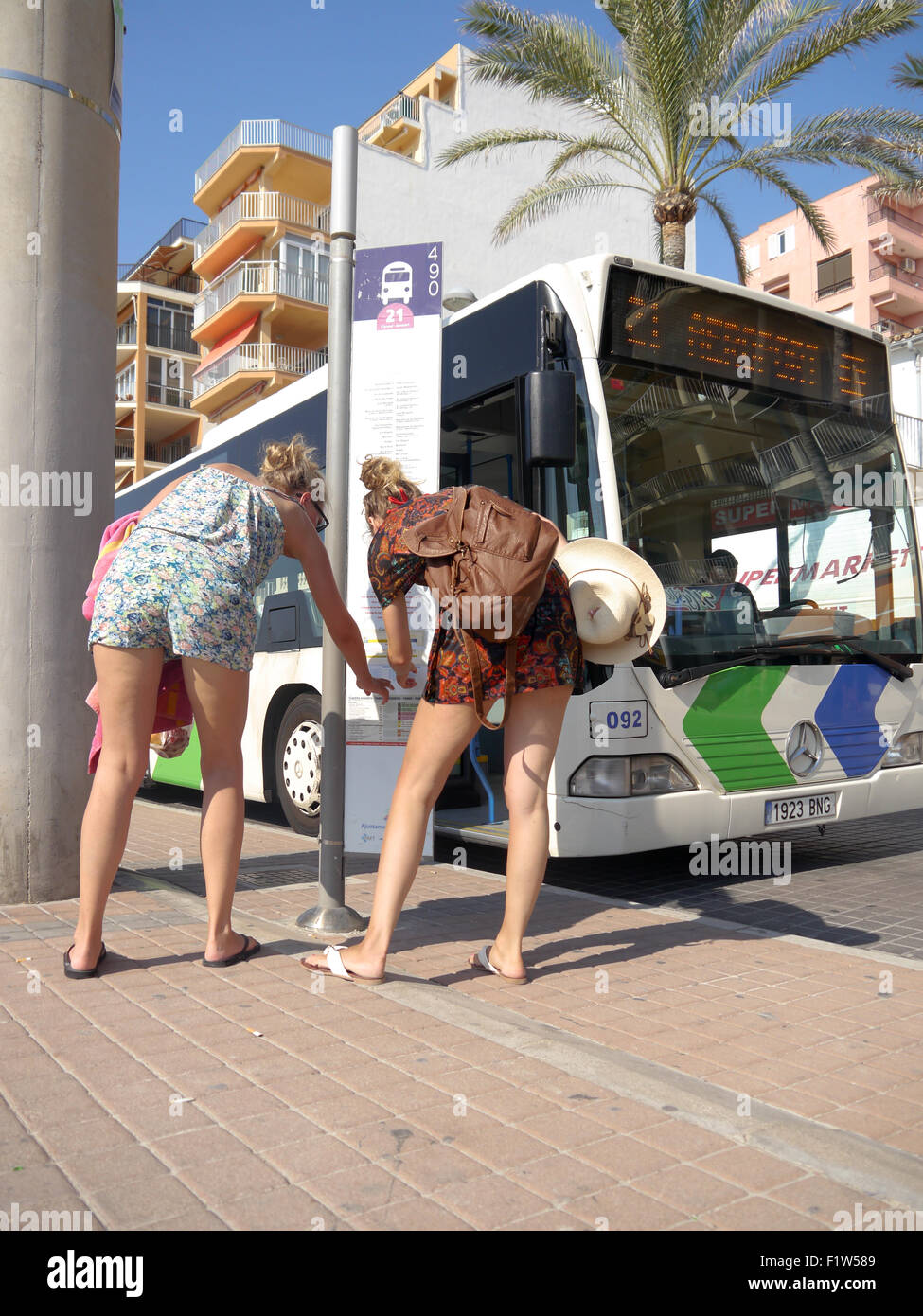 Two young ladies looking at a bus timetable beside an EMT bus in El Arenal, Mallorca, Spain - Stock Image
