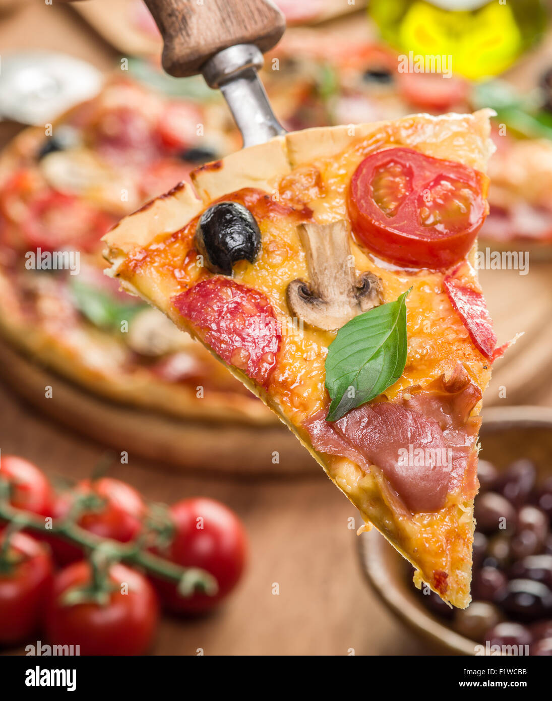Piece of pizza with mushrooms, ham and tomatoes. Top view. - Stock Image