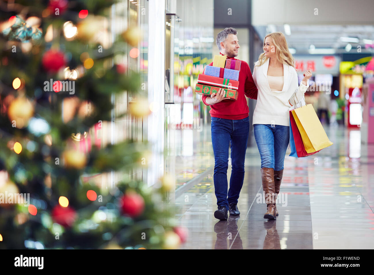 Happy couple looking for Christmas presents in the mall - Stock Image