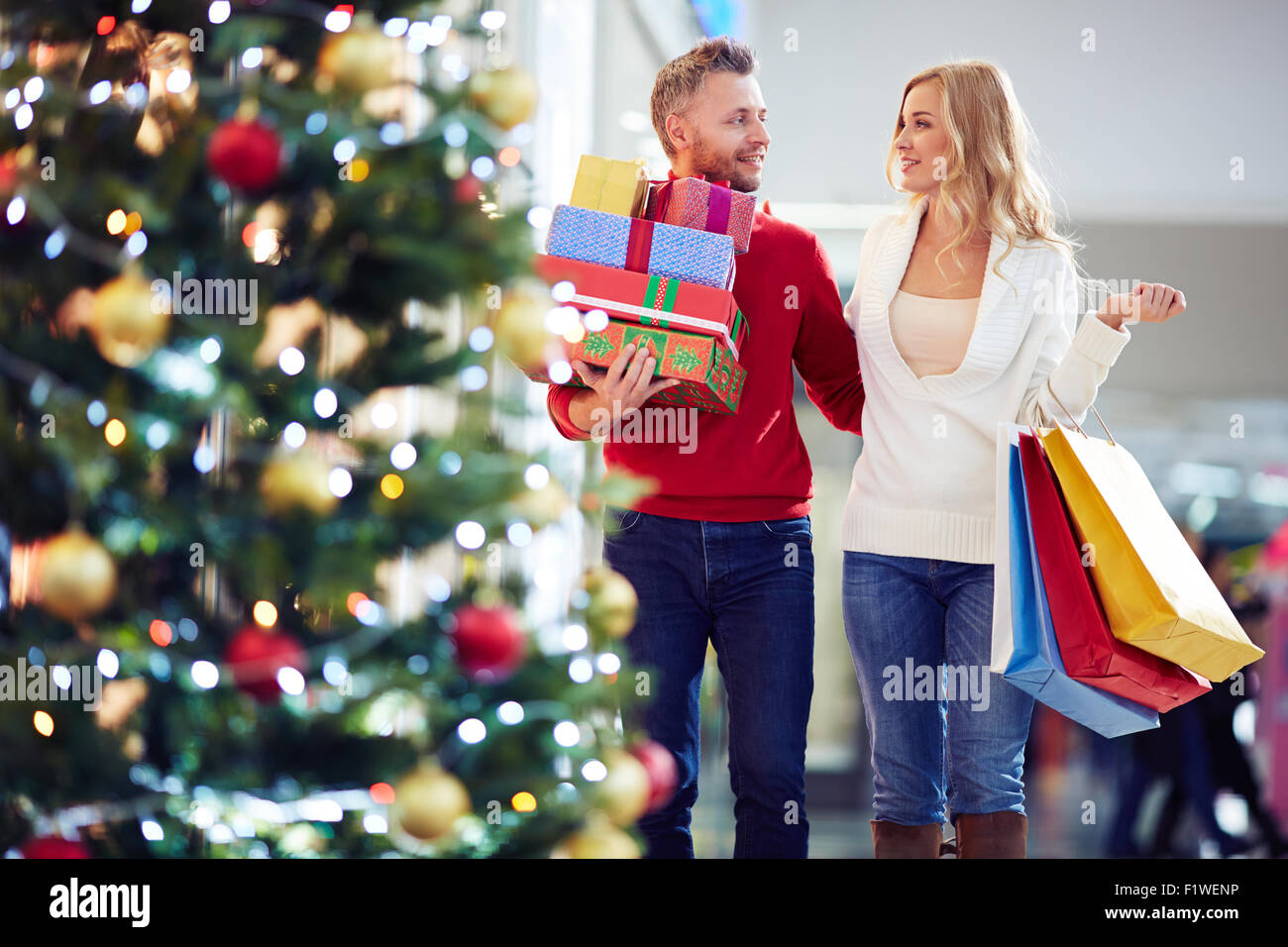 Affectionate couple carrying Christmas presents while shopping in the mall - Stock Image