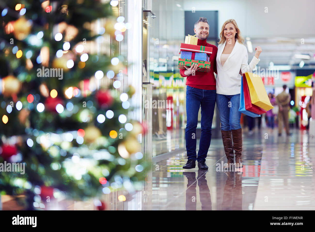 Affectionate couple buying Christmas presents on holiday eve - Stock Image