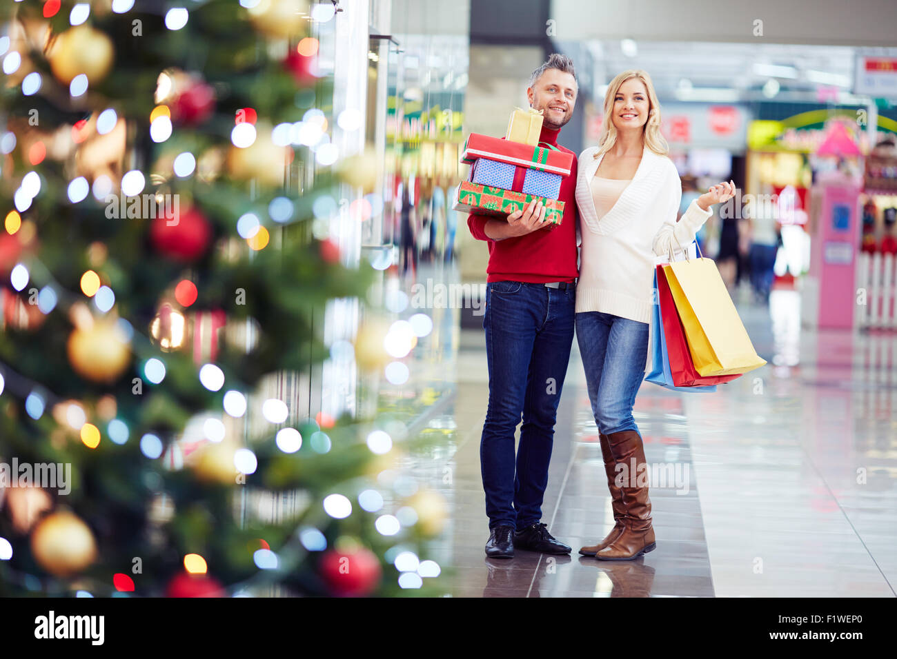 Affectionate couple with gifts shopping in the mall before Christmas - Stock Image