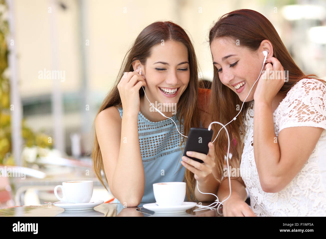 Friends sharing and listening to music with earphones and smartphone in a coffee shop - Stock Image