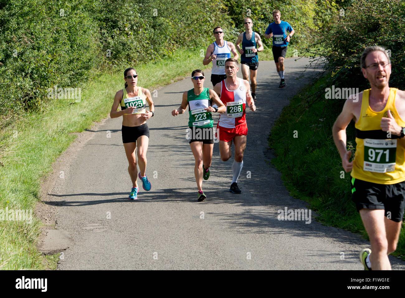 Half marathon runners on a country road, Warwickshire, UK - Stock Image