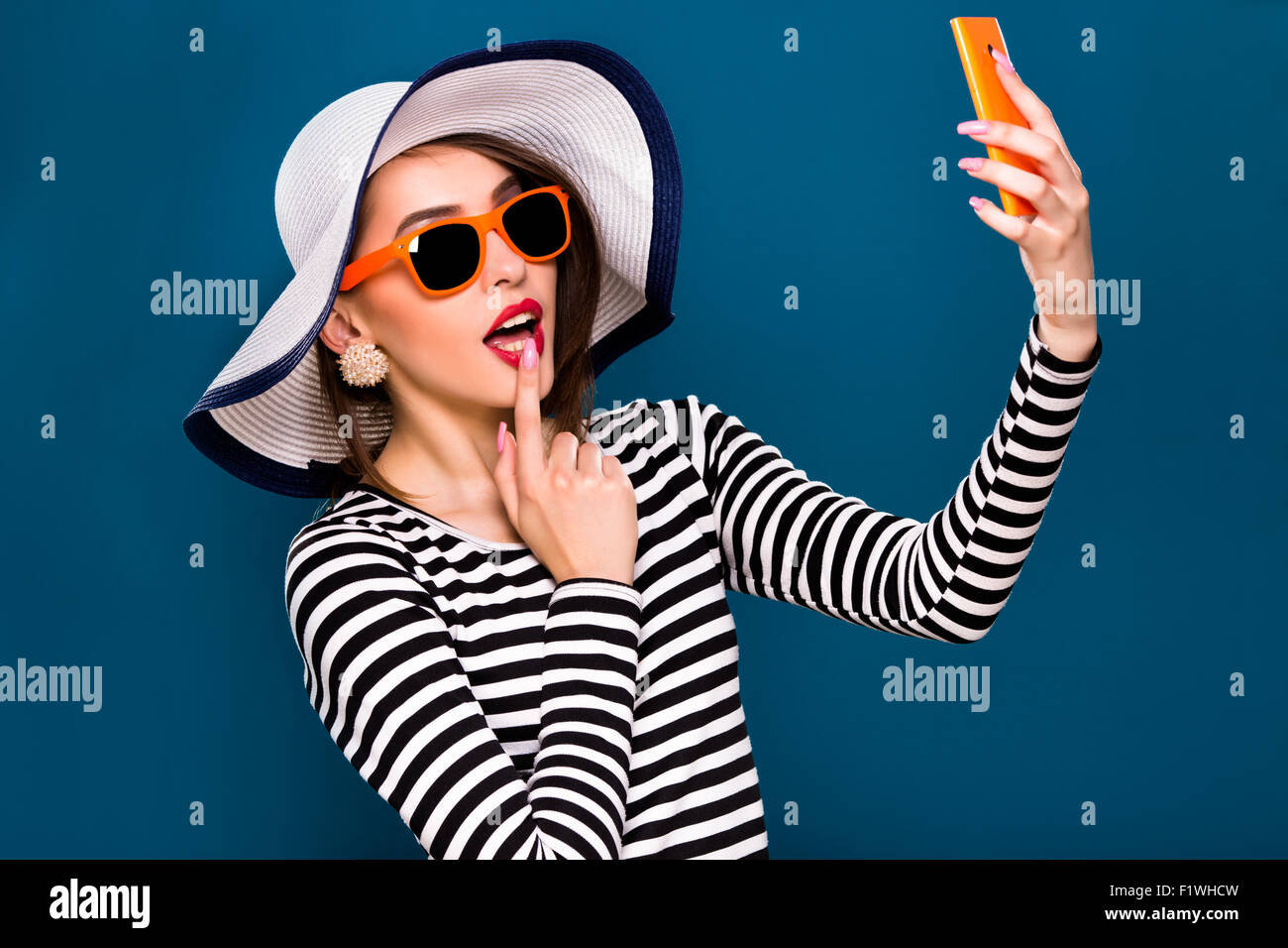 Coquettish young woman is taking selfie with her smart phone - Stock Image