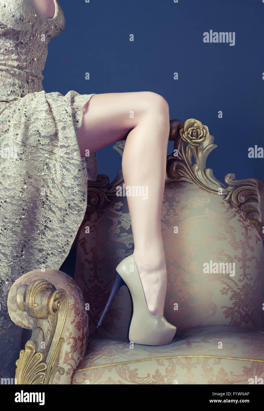 Beautiful slim leg on the luxury vintage armchair - Stock Image