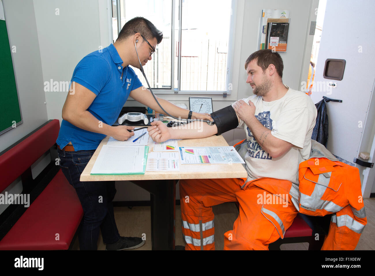Construction workers taking blood pressure test and general health check on site, England, UK - Stock Image
