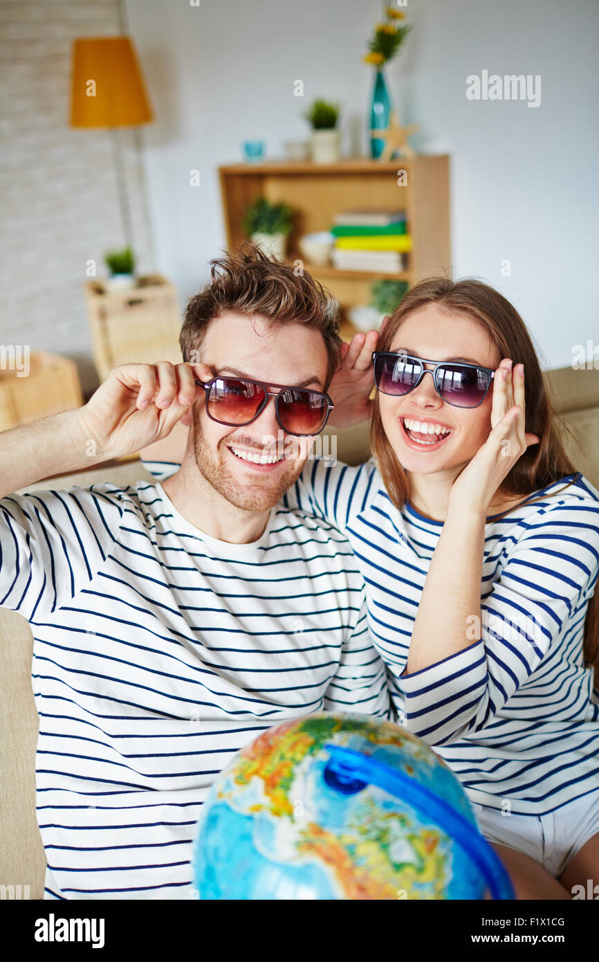 Happy couple in sunglasses looking at camera with smiles - Stock Image