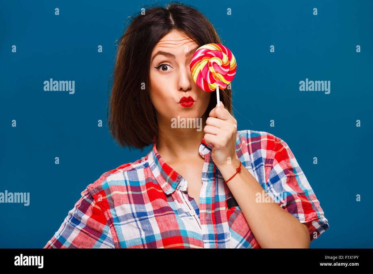 Cute coquettish girl posing with colored candy in studio - Stock Image