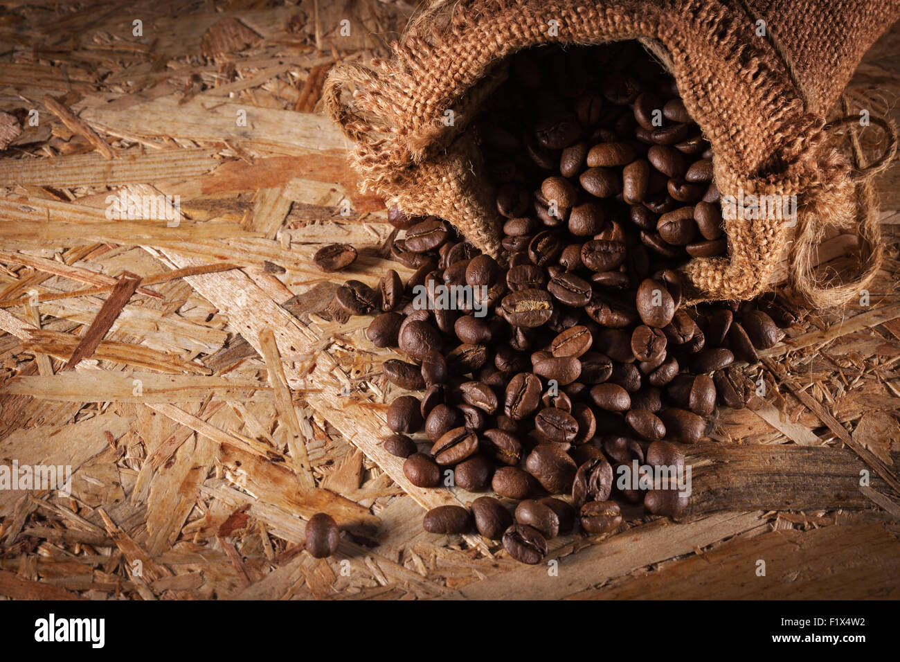 bag with coffee beans isolated on the wooden background. - Stock Image