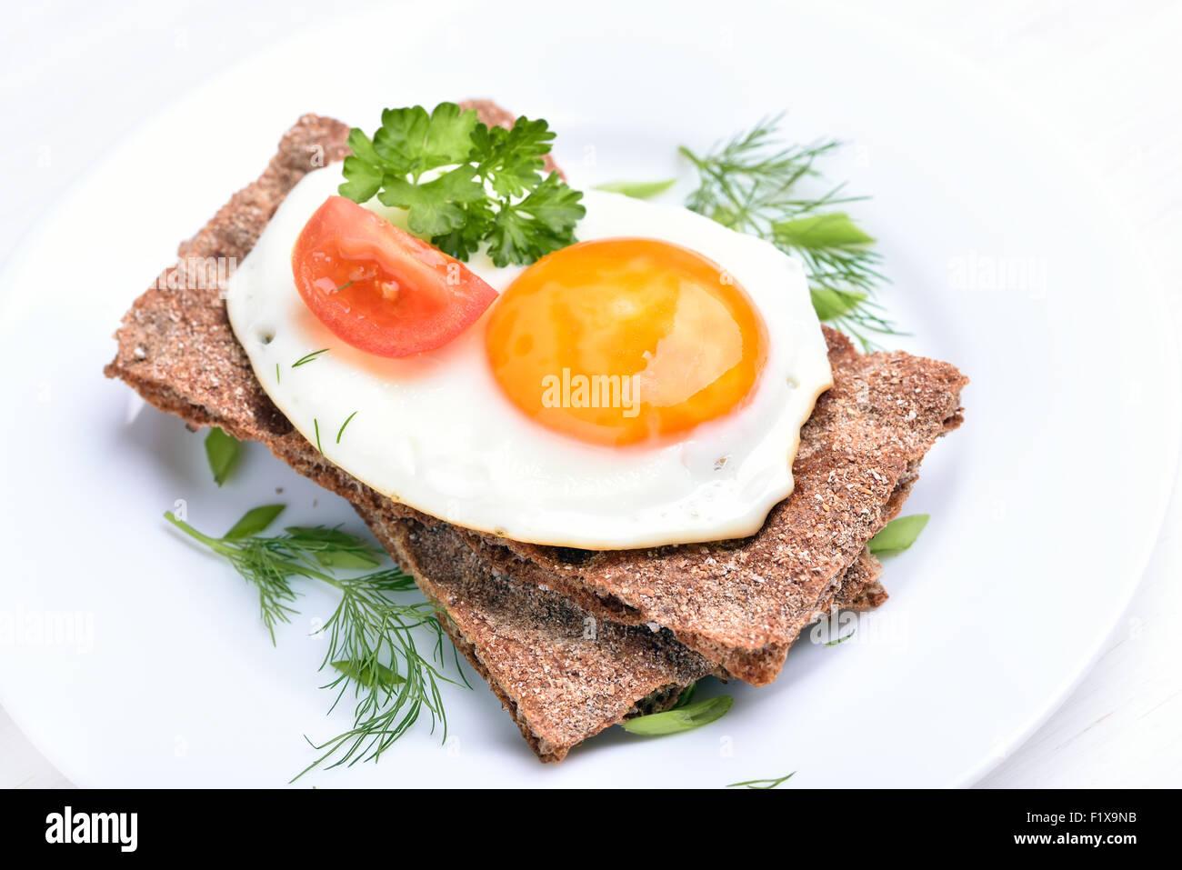 Fried egg, parsley and tomato slice on crispbread - Stock Image