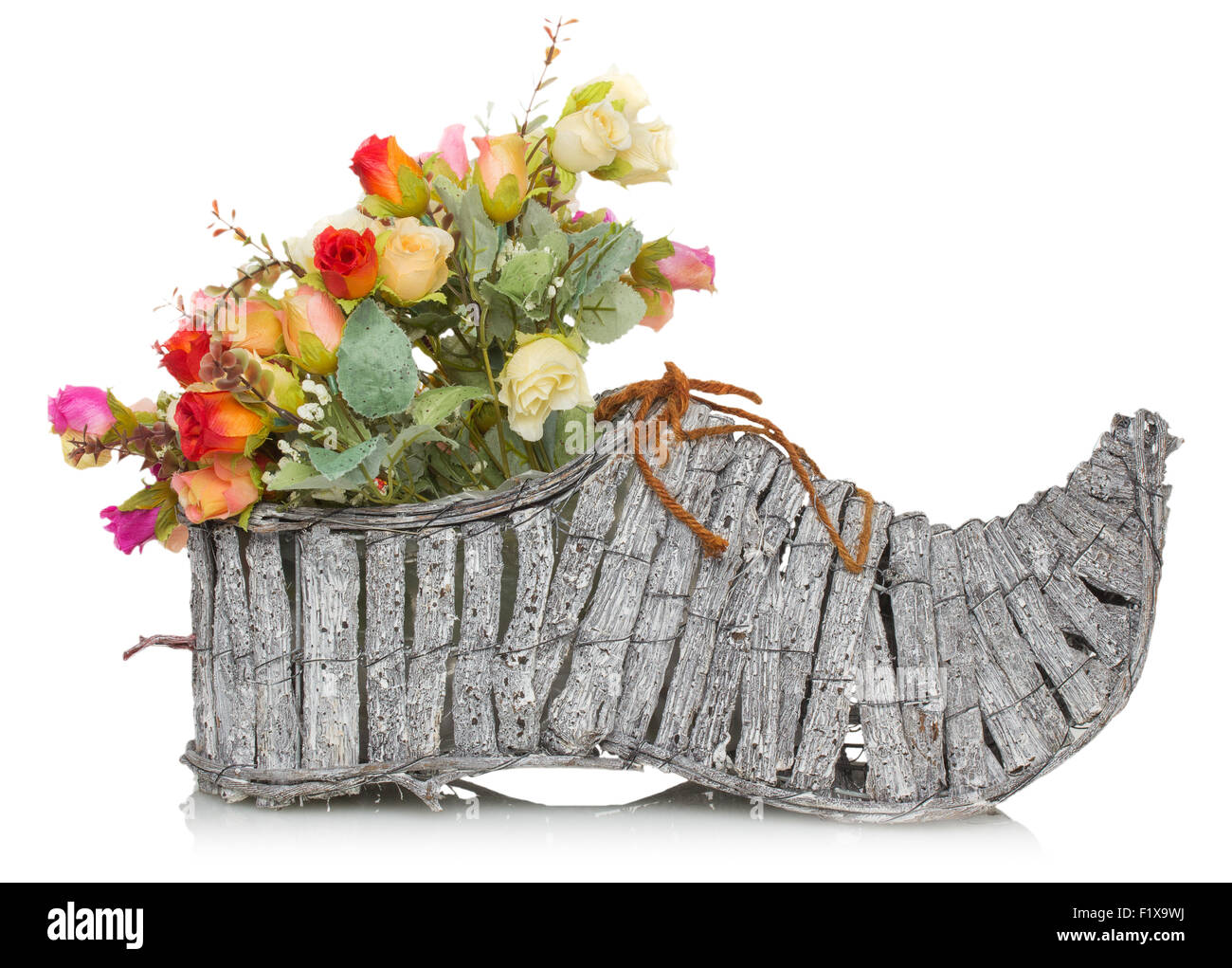 bouquet of flower in wooden boot on a white background. - Stock Image