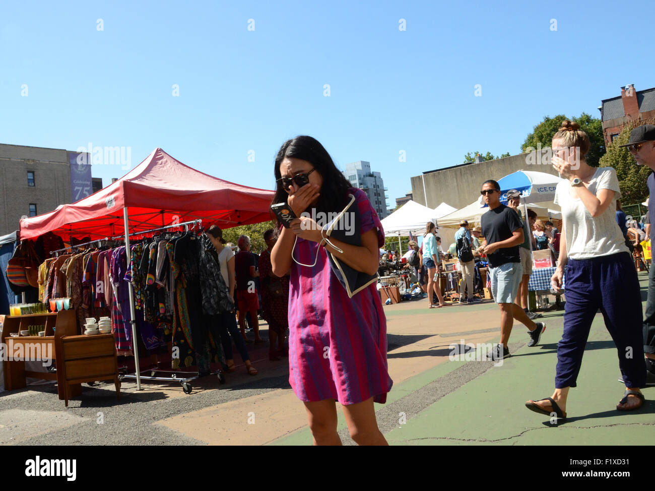 woman reacts with shock at phone message brooklyn flea market new york - Stock Image